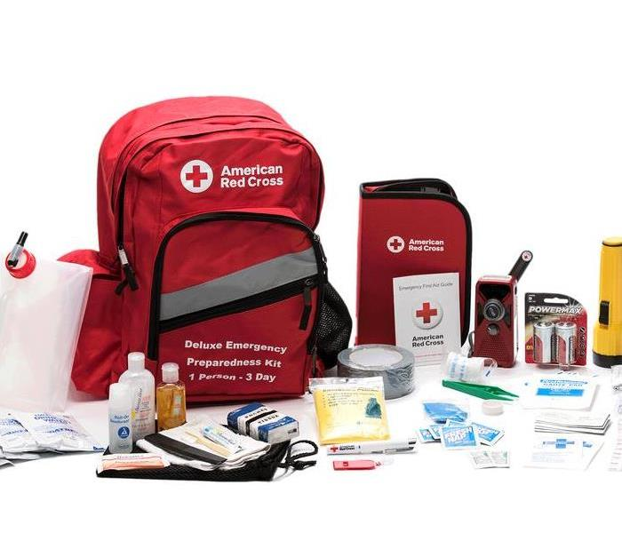 Photo shows American Red Cross Emergency Kit supplies including: batteries, flashlight, water, first aid kit, medicine, etc.