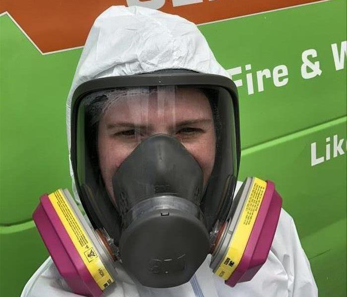 A SERVPRO of Mandarin employee dressed in a full face respirator and coveralls standing in front of a SERVPRO van.
