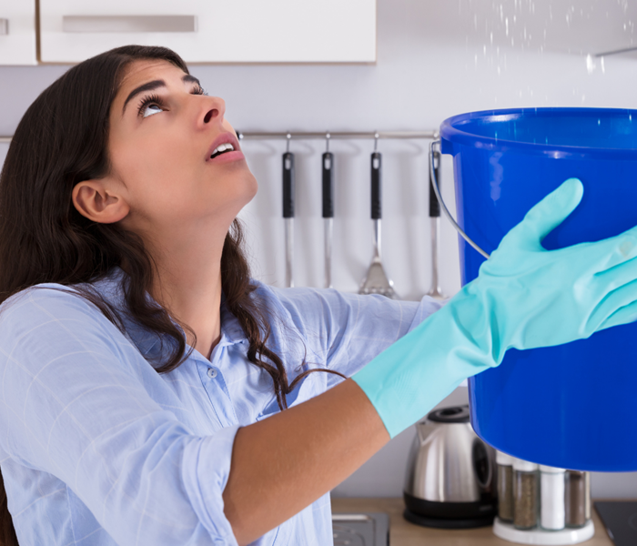 Women with gloves holding up a bucket to catch water from a leak.