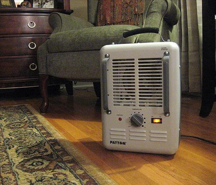 Image shows space heater sitting on the carpet in a home.