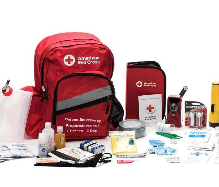 Photo shows an emergency kit from the American Red Cross with a backpack, water bottles, and first aid supplies.